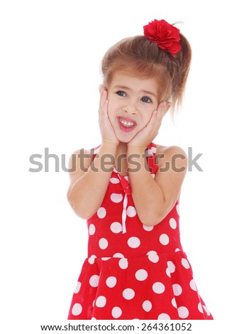 A little girl in a red dress with white polka dots kept hold of the cheeks, isolated on white background - stock photo
