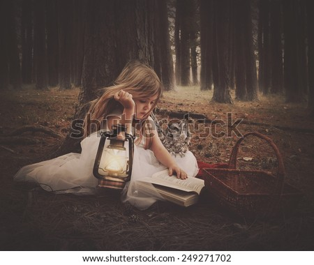 A little girl in a white dress is reading on old story book with an owl and glowing lantern in the dark woods for an education or imagination concept. - stock photo