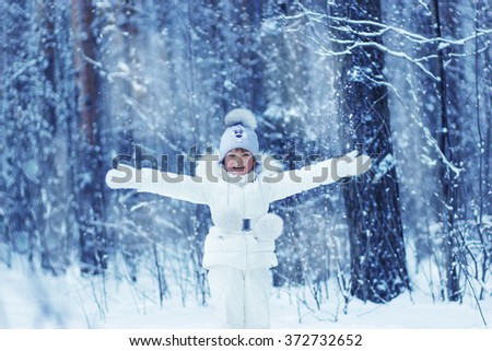 a little girl in a white suit in the winter woods throws snow - stock photo
