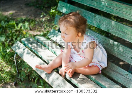 A little girl in a white sundress sitting on a park bench