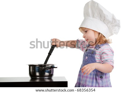 a little girl in cook hat cooks - stock photo