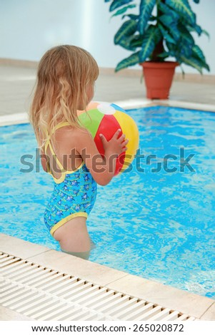 a little girl in the water pool with a ball - stock photo