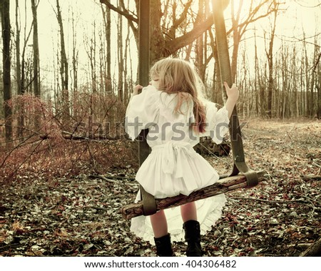 A little girl is alone swinging on an old vintage swing in the woods with trees for a fear, hope or sadness concept - stock photo