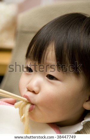 A little girl is eating a meal.