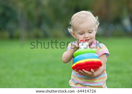 A little girl is holding toy pyramid while walking outside - stock photo
