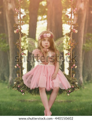A little girl is sitting in the woods on a swing with sparkle fairy wings blowing magical dust for an imagination or fairy tale concept.  - stock photo