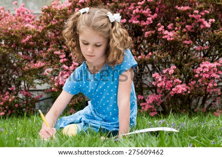A little girl  is using a pencil to draw in a notebook.  She is wearing a blue polka dot dress and has white bows in her blond hair.  She is sitting outside in front of pink azalea bushes. - stock photo