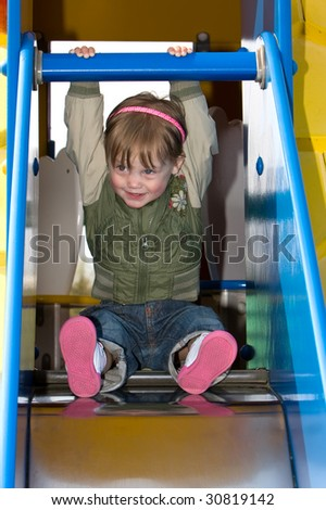 A little girl is willing to slide down. - stock photo