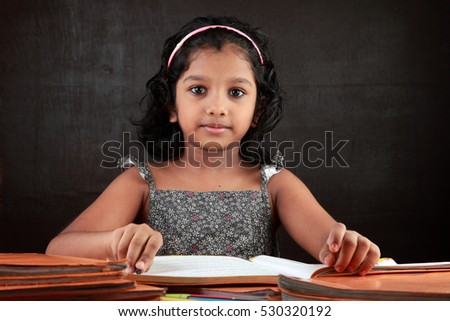 A little girl looks as does her homework in the study room