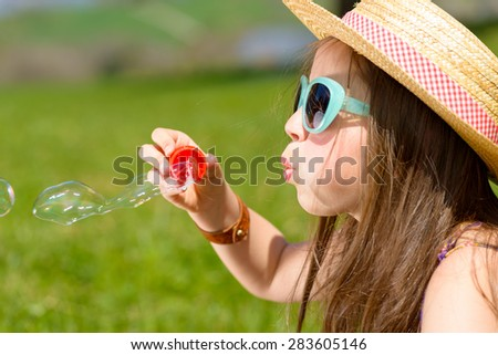 a little girl making soap bubbles in nature - stock photo