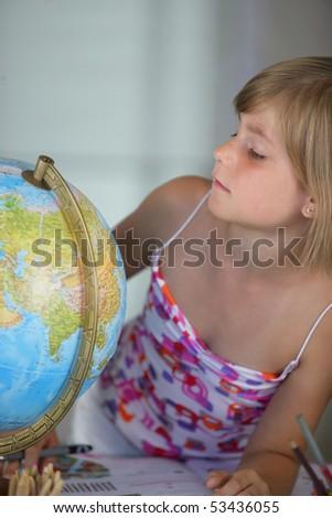 A little girl making turn a globe - stock photo