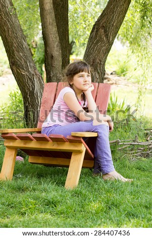 a little girl of 8 years, brunette in purple jeans, a pink T-shirt, summer, sitting under a tree in the chair