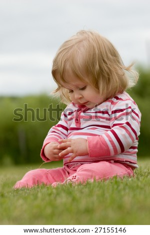A little girl playing in the grass - stock photo
