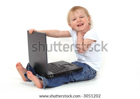 A little girl playing with a laptop - stock photo