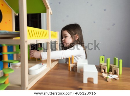 A little girl playing with dollhouse - stock photo