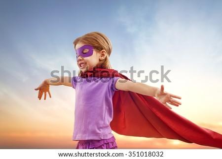 a little girl plays superhero - stock photo
