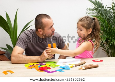 A little girl practicing the alphabet with her father - stock photo