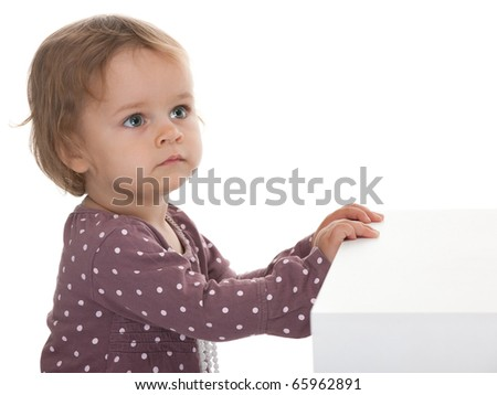 A little girl puts her hands on the white cub like it is a piano; isolated on the white background - stock photo