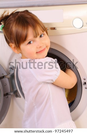 A little girl puts the towels into the washing machine - stock photo