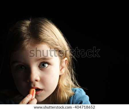 A little girl putting on chapstick