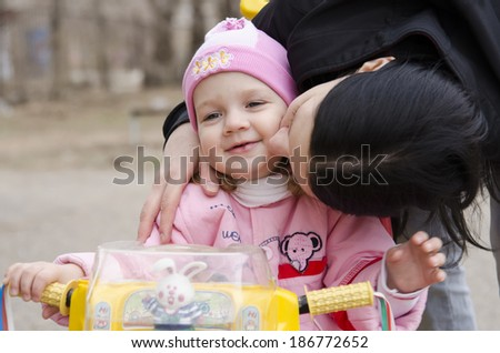 A little girl sat on the bike. Mom leaned over to her and kisses her. A warm spring day.