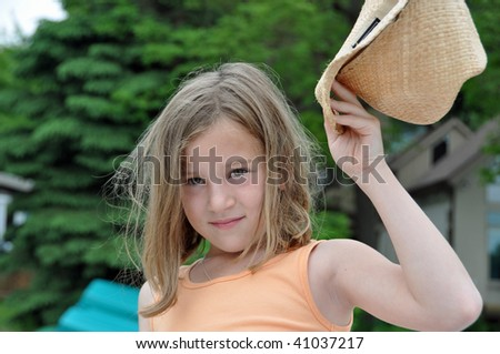 a little girl shows off and raises her cowboy hat - stock photo