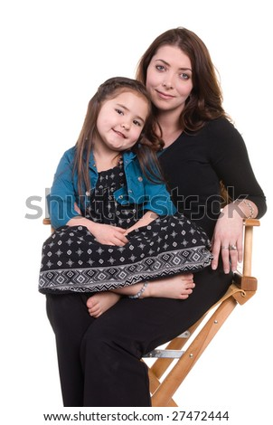 A little girl sits cross legged in her mother's lap. - stock photo