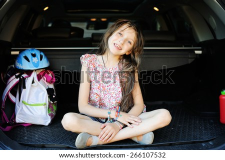 a little girl sitting in the car with backpack and helmet - stock photo