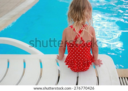 a little girl sitting near the pool - stock photo