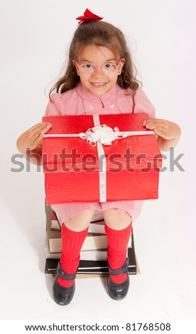 A little girl sitting on a pile of books holding big red and white present - stock photo