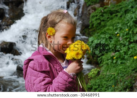 A little girl smelling yellow flowers and smiling, with a pink coat. In the background there is waterfall and green plants.