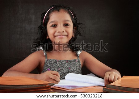 A little girl smiles as does her homework in the study room