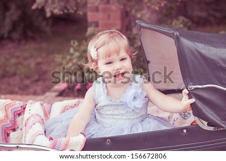 A little girl smiling in a old-fashioned buggy. - stock photo