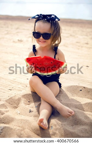 a little girl stands on the shore of the beach in a black bathing suit and black glasses eating juicy watermelon sitting - stock photo