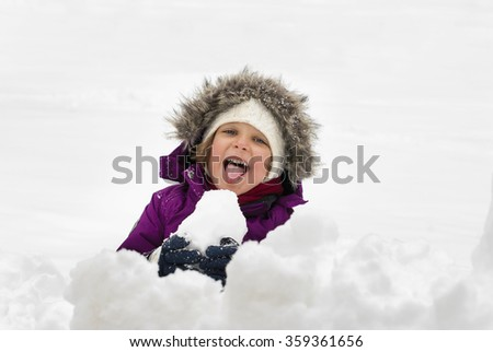 A little girl sticking out tongue while eating snow. - stock photo