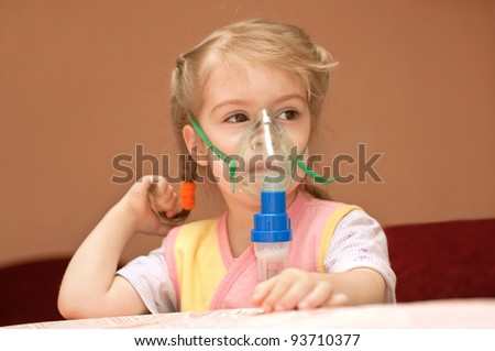 A little girl three years doing inhalation - stock photo