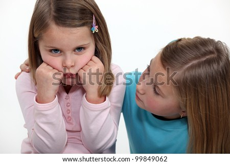 A little girl trying to cheer up her sister. - stock photo
