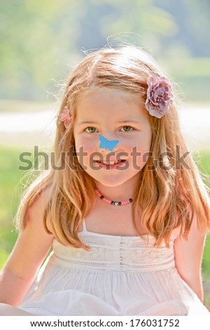 A little girl wearing floral hair clips outside.