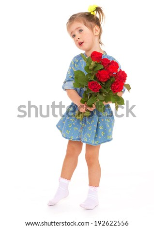 A little girl with a bouquet of red roses in his hands standing on a white background