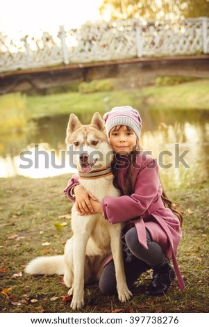 A little girl with a husky dog sitting in autumn Park