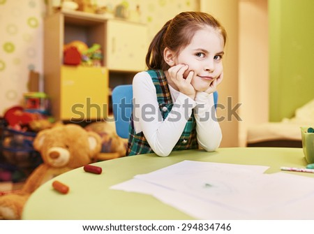 A little girl with a naughty smirk on her face in her playroom - stock photo