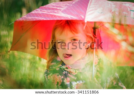 a little girl with a red umbrella shows tongue and stands at the tree in the forest