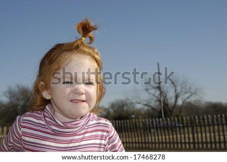 A little girl with her hair in a pony tail grinning