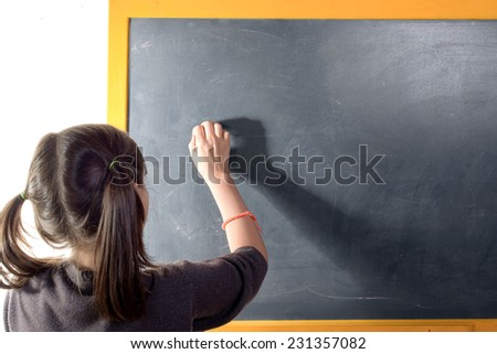 a little girl with pigtails writes on a blackboard - stock photo