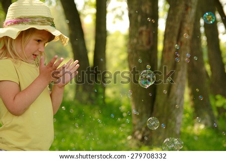 a little girl with soap bubbles - stock photo