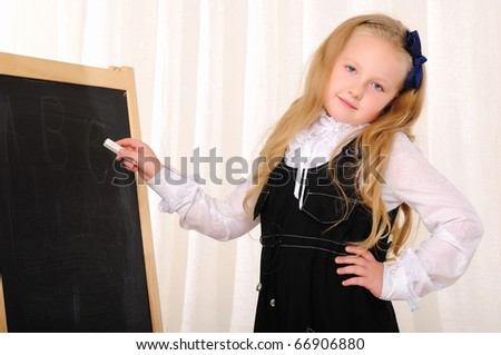 A little girl wrote a white chalk on a blackboard.