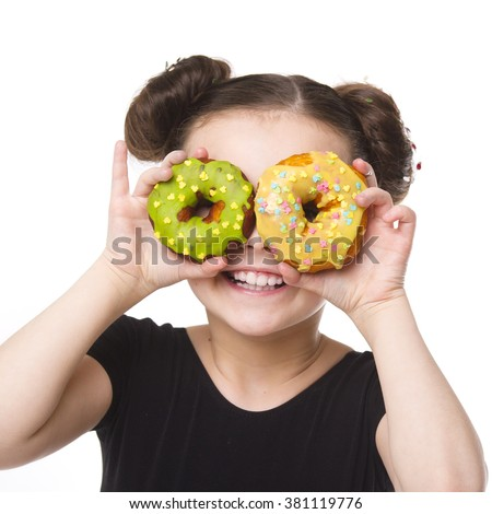 A little happy girl eating and playing with donuts. Smiling joyful kid portrait. - stock photo