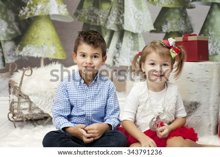 A little happy lovely girl sitting on the floor with her big brother against Christmas Tree and a fireplace and opening Christmas presents wrapped in golden paper with curiosity. Kids and holidays   - stock photo