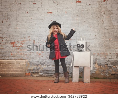 A little hipster child wearing a cool hat is holding a tablet with her toy robot friend downtown for a happiness or technology concept. - stock photo