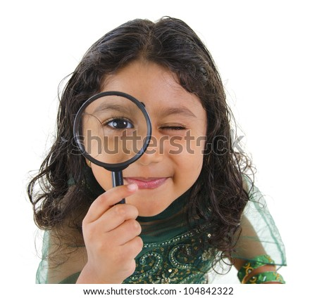 A little Indian girl peers at the camera through a magnifying glass, isolated on white background - stock photo